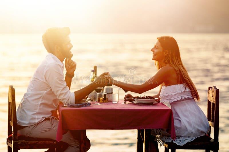 人、假期、爱和浪漫史概念 享受在海滩的年轻夫妇一顿浪漫晚餐 图库摄影