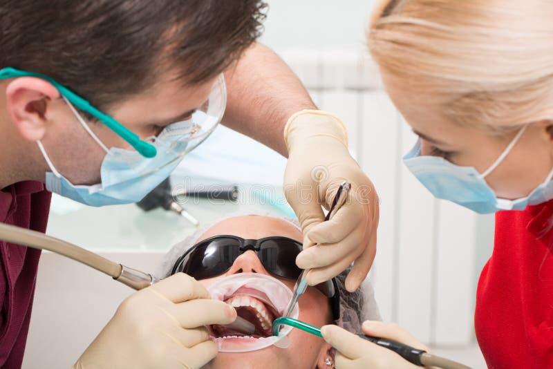 人、医学、口腔医学和医疗保健概念-男性牙医和助理有对待女性的唾液喷射器的 库存图片