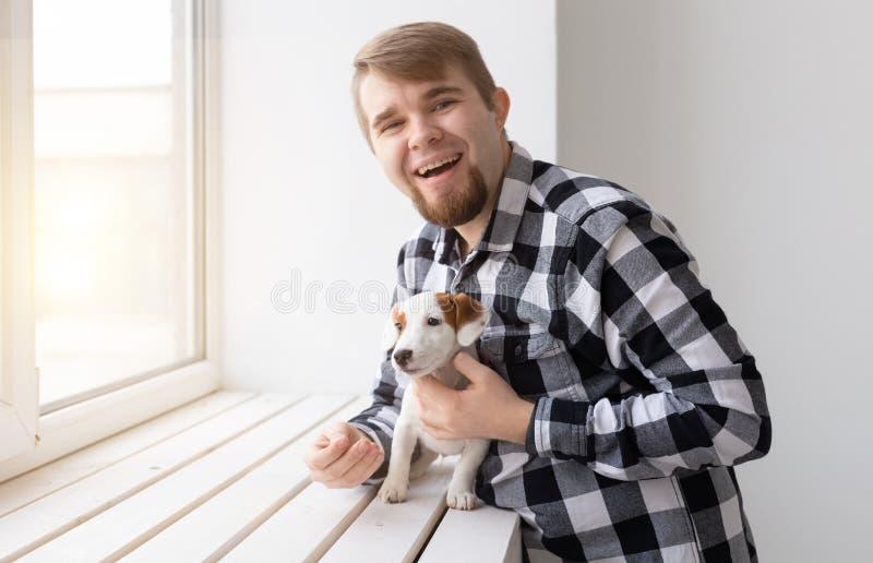 人、宠物和动物概念-拥抱小狗的年轻人在白色背景的窗口附近 免版税库存照片