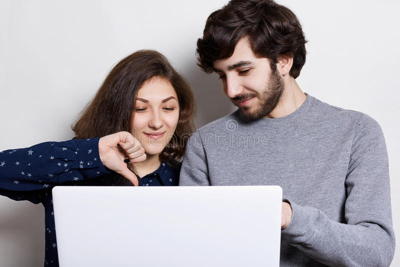 人、技术和通信概念 时髦的有胡子的人和他的使用膝上型计算机和浏览互联网的女朋友为在网上 库存图片