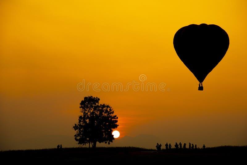 人、树和热空气气球的剪影在五颜六色的日落的与在背景和拷贝空间的大太阳 库存照片