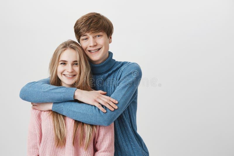 人、爱和关系概念 愉快的微笑的夫妇甜射击穿戴了偶然拥抱,笑 库存照片
