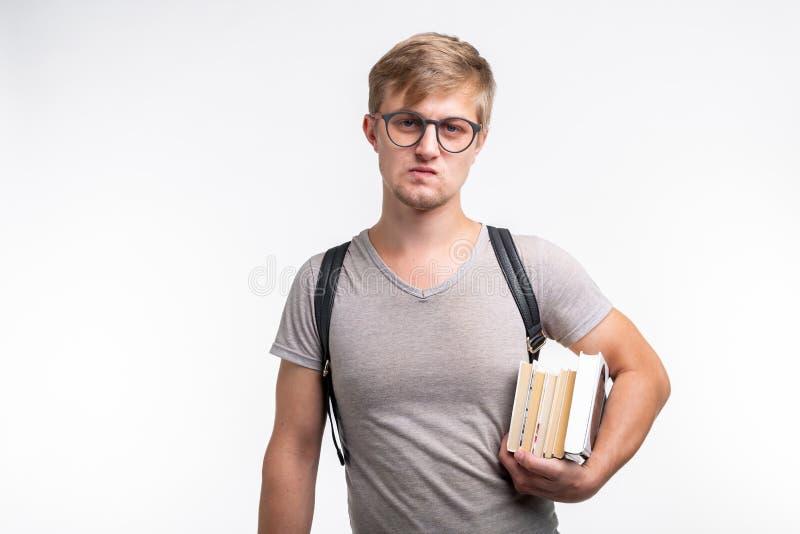 人、知识和教育概念-在灰色T恤杉打扮的一个学生人的画象在他的手上拿着书 免版税库存照片