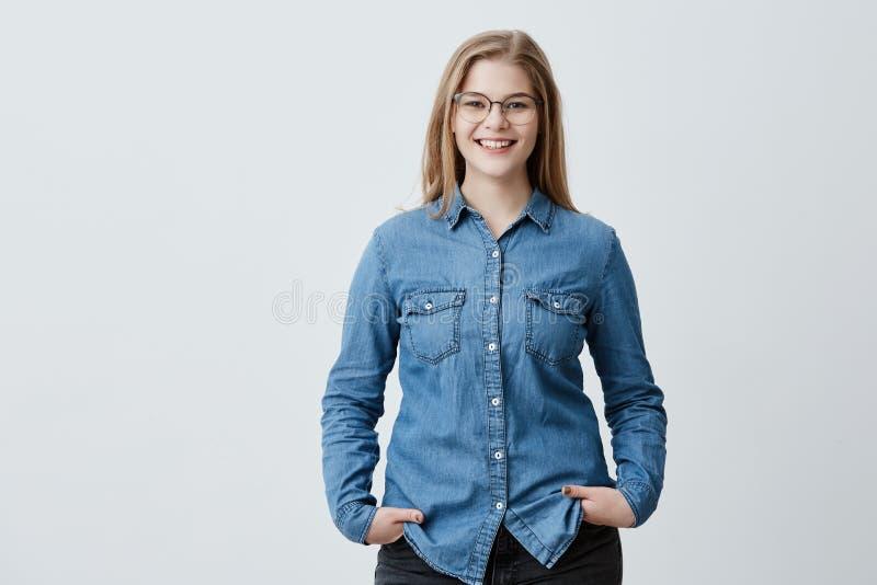 人、秀丽和生活方式概念 有眼镜的可爱的肉欲的白肤金发的妇女和宽微笑在牛仔布穿戴了 免版税图库摄影
