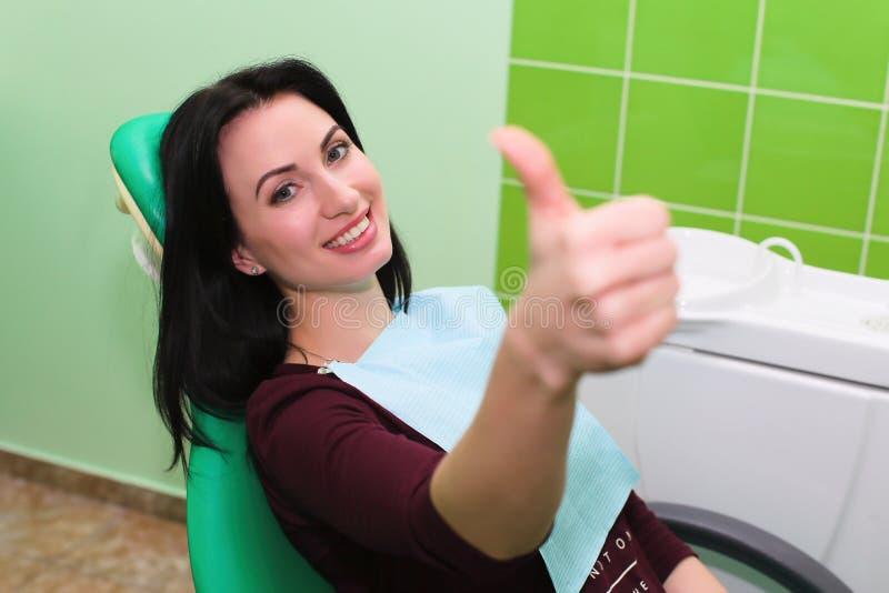 人、医学、口腔医学和医疗保健概念-显示赞许的愉快的耐心女孩在牙齿诊所办公室 图库摄影