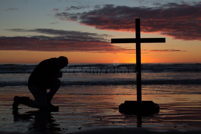 人下跪十字架 免版税库存图片