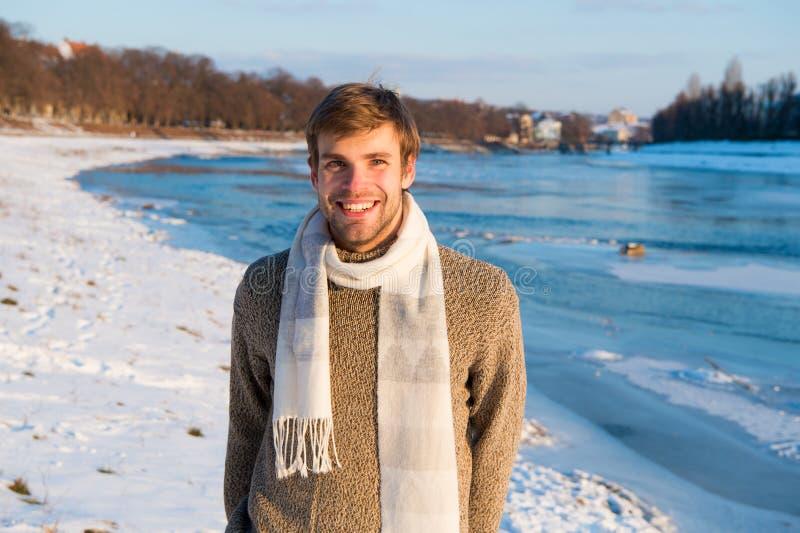 人不剃须的英俊的行家在针织品毛线衣羊毛围巾立场冻结的河背景中 冬天风景秀丽 免版税库存照片