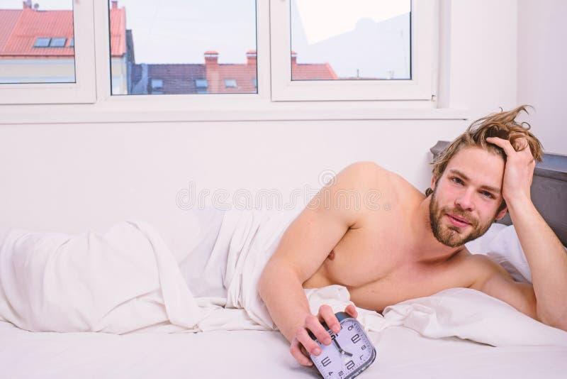 人不剃须的被放置的床举行闹钟 有人不剃须的有胡子的警惕的面孔休息棍子日程表同样上床时间苏醒 免版税库存图片