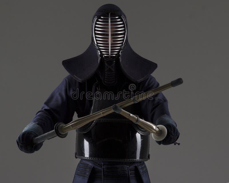 人与两把竹剑的kendo战斗机画象在传统制服 免版税图库摄影