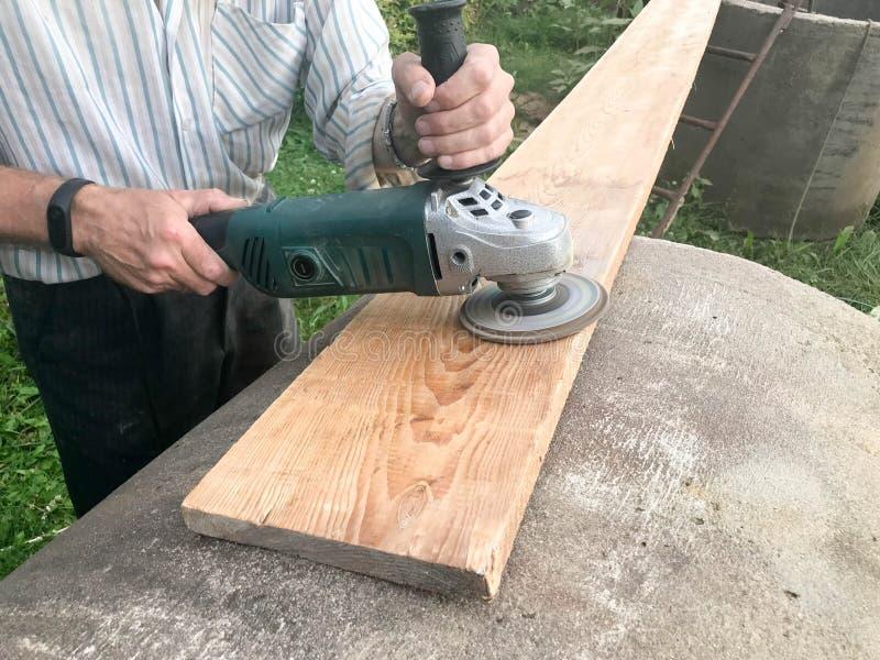 人与他的手一起使用,为研磨机,为研和擦亮表面的电工具研盘  库存照片