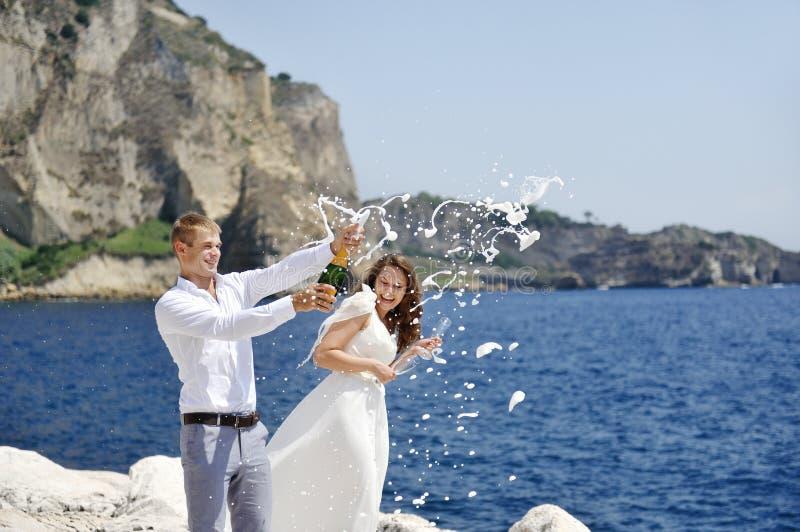 年轻人与吐露香槟的夫妇结婚由海在他们的婚礼以后 库存图片