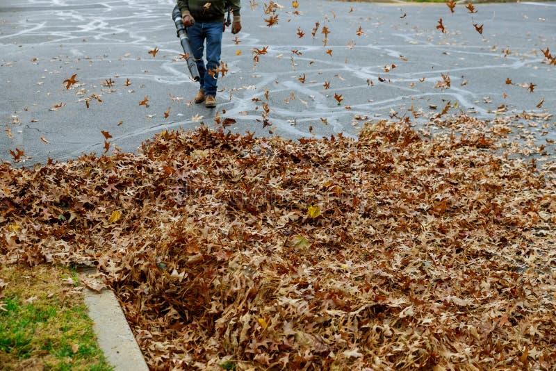 人与吹叶机一起使用叶子在一好日子上上下下打旋 免版税库存图片