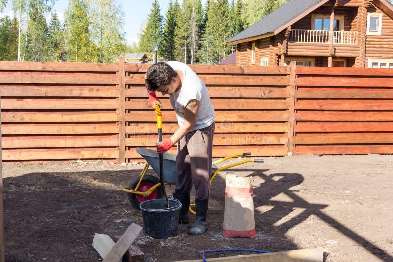 人与在桶的铁锹混合水泥 库存图片