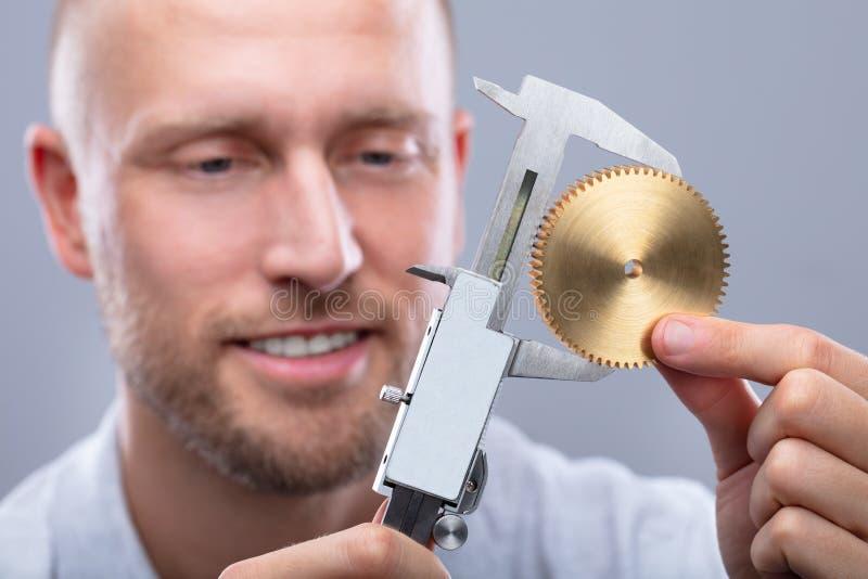 人与数字游标卡尺的测量的齿轮的大小 免版税库存照片