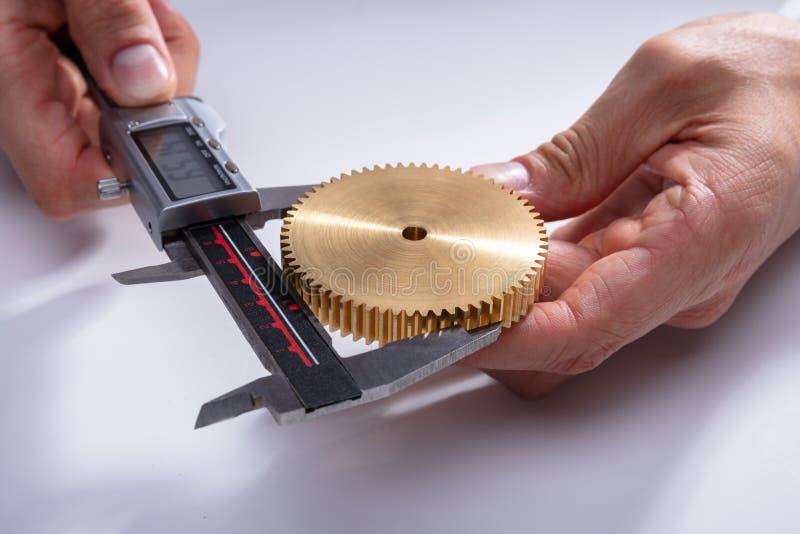 人与数字轮尺的测量的齿轮的大小 库存照片