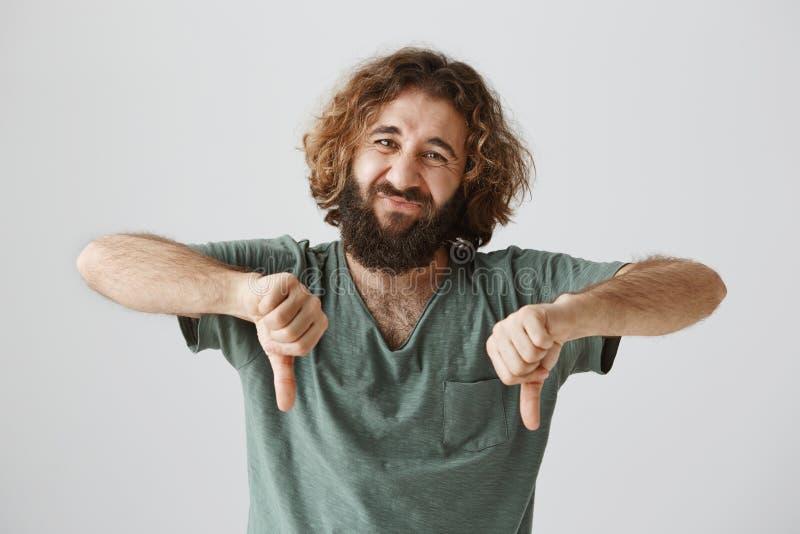 人与肢体语言的表达的反感 演播室显示射击了有胡子和卷发的英俊的阿拉伯人皱眉和 免版税库存图片