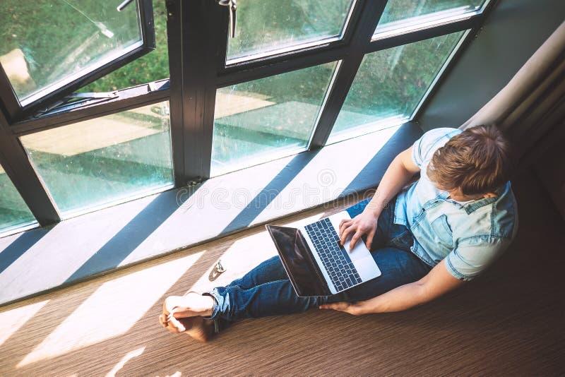 人与膝上型计算机一起使用坐地板在开窗口附近 库存图片