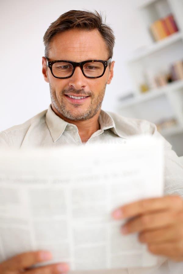 人与镜片的读书报纸 免版税库存图片
