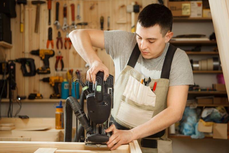 人与雕刻设备一起使用在车间 Chinseling凹线 免版税库存图片