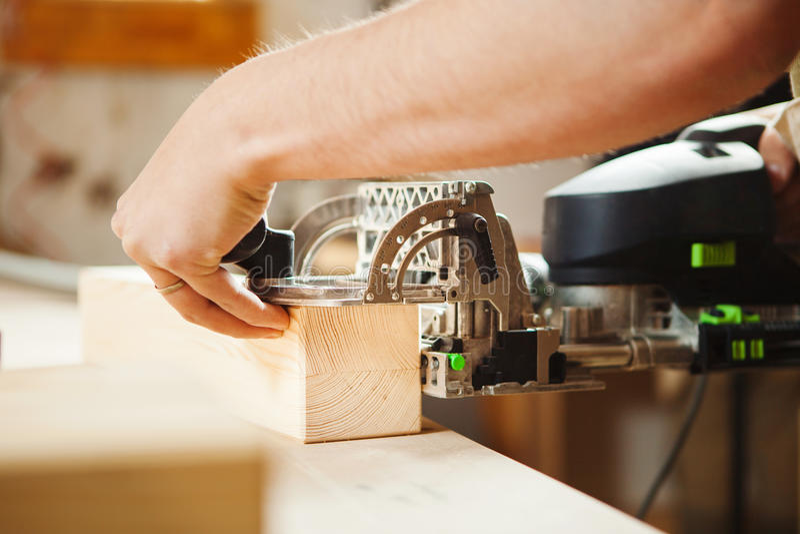 人与雕刻设备一起使用在车间 电子设备 免版税库存照片
