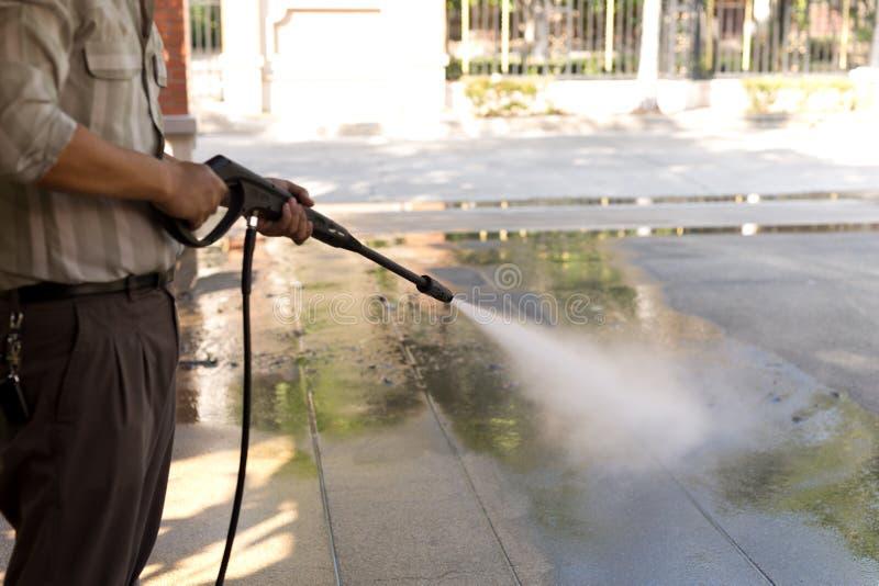人与高压喷水的清洁石头 免版税库存图片