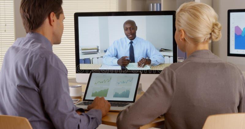 黑人业务经理遥远地谈话与雇员 免版税图库摄影