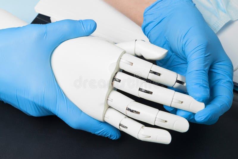 人为机器人假肢 医生握网络手 免版税库存照片