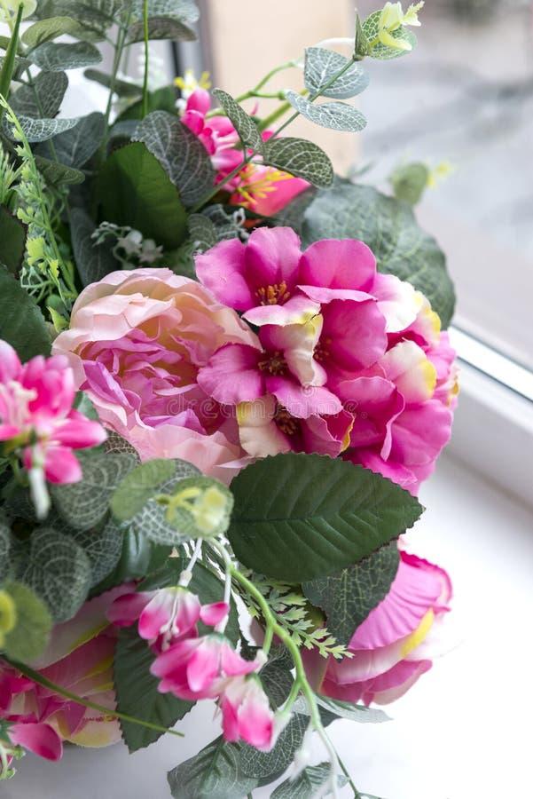 人为桃红色花花束在窗口、牡丹和八仙花属附近的 免版税库存图片