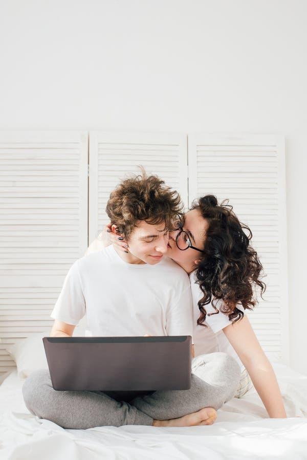 人为膝上型计算机,女孩工作亲吻他 库存图片