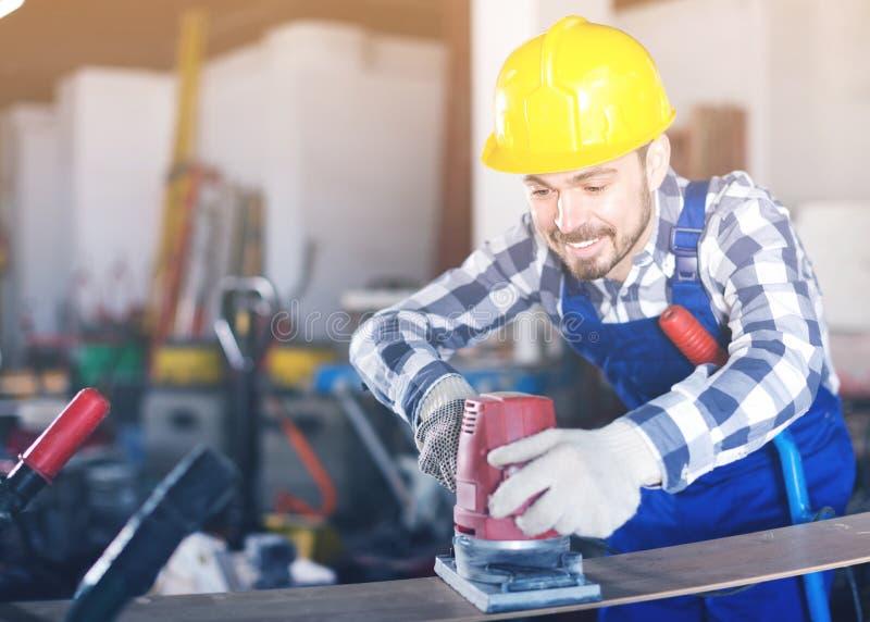 年轻人为建筑工作使用研磨机 免版税库存图片