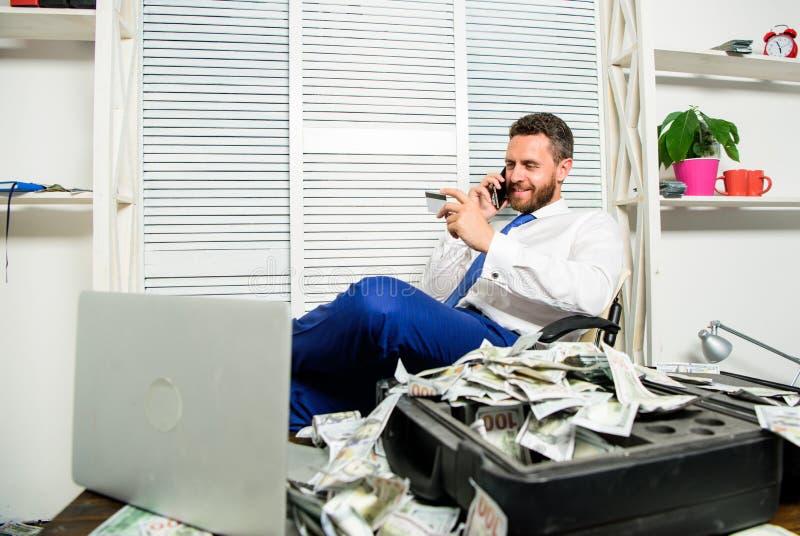 人举行塑料银行卡 人成功的商人电话交谈要求服务 商人富有的有胡子的人坐 库存照片
