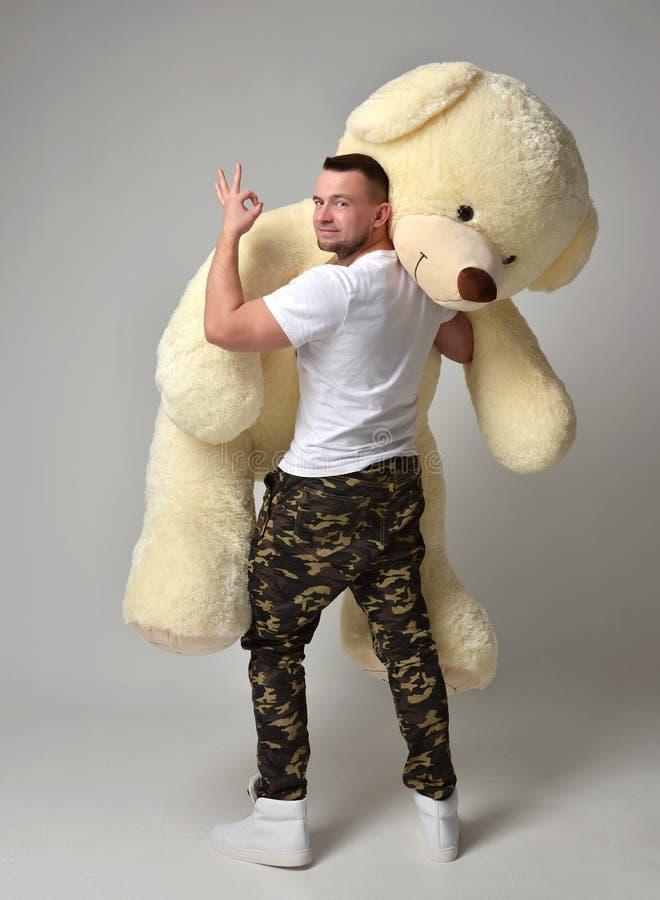 人举行大玩具熊软的玩具作为对他的女朋友的一个礼物 库存图片