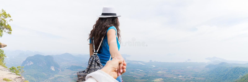人举行妇女手,旅游加上在山上面后面后方全景视图的背包享受美好的风景 免版税图库摄影