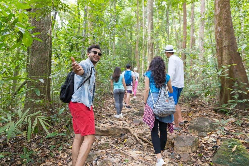 人举行手欢迎与迁徙在森林道路后面背面图、年轻人和妇女的背包的人小组远足的 库存照片