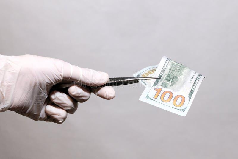 人举行的手在白色医疗手套的100美元与镊子 免版税库存图片