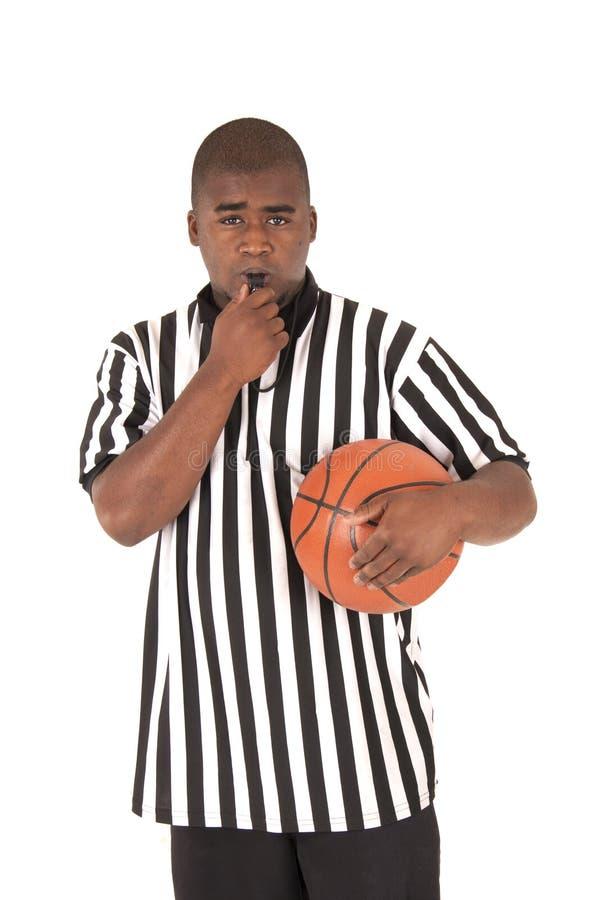 黑人举行篮球的裁判员吹的口哨 免版税库存图片