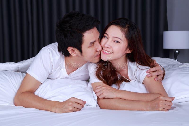 人亲吻他面颊的美丽的微笑的妻子在床上 库存照片