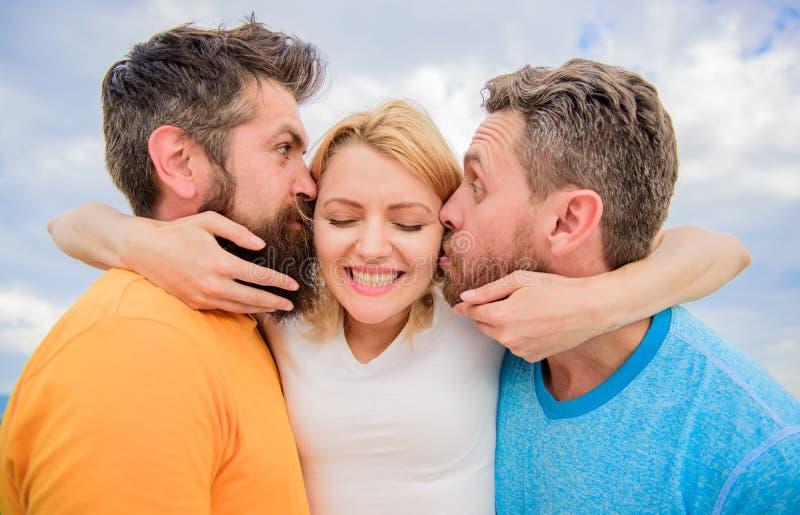 人亲吻同样女孩面颊 夫人享受浪漫联系两位钦佩者 人爱上同样妇女 她喜欢男性 免版税图库摄影