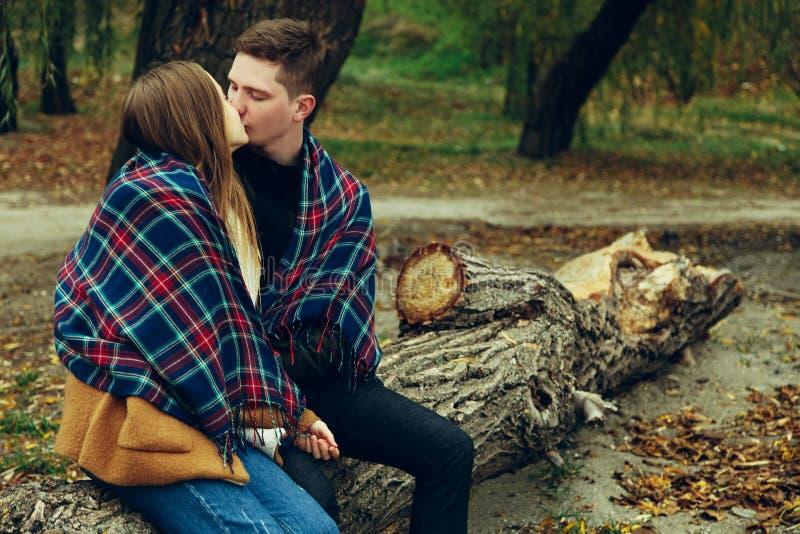 人亲吻在格子花呢披肩包裹的女孩 图库摄影