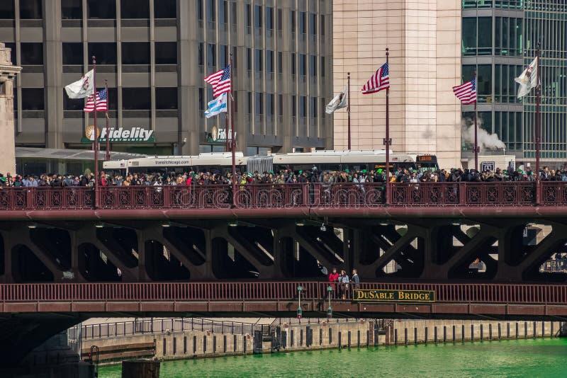 人人群在密执安Ave/DuSable桥梁一起聚集观看芝加哥河是被洗染的绿色的 免版税库存照片