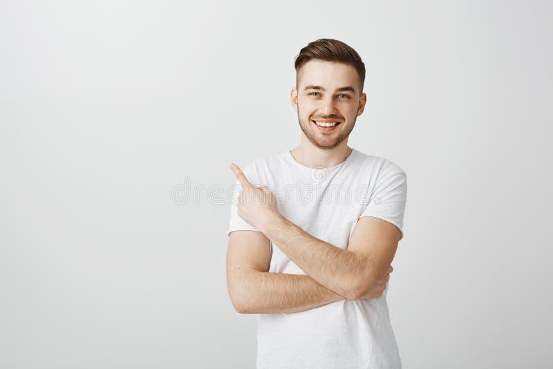 人介绍朋友给他的伙伴在指向左与食指和微笑以喜悦无忧无虑的党期间 免版税库存图片