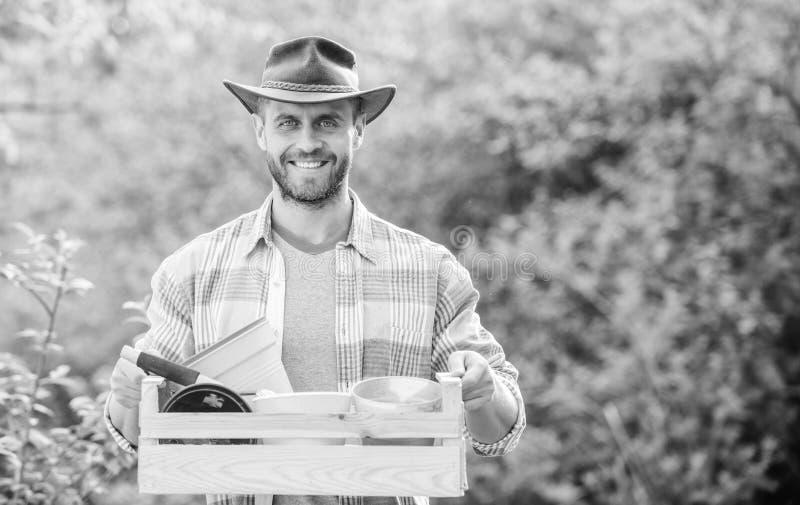 人从事园艺 性感的有花盆的农夫举行木箱 E E Eco?? 种田和 库存图片