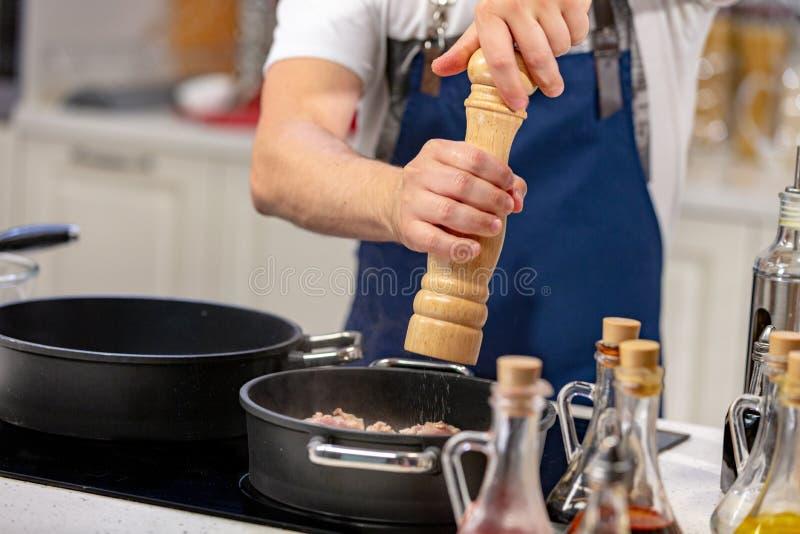 人从磨房加碎胡椒入在火炉的煎锅 ooking的概念 免版税库存照片