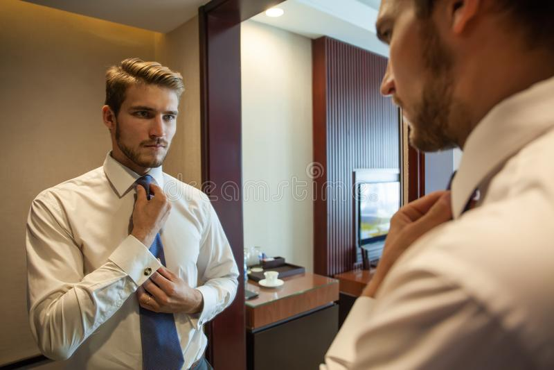 人们、事务、时尚和衣物概念-接近衬衣的人装饰和在家调整在脖子的领带 免版税库存图片