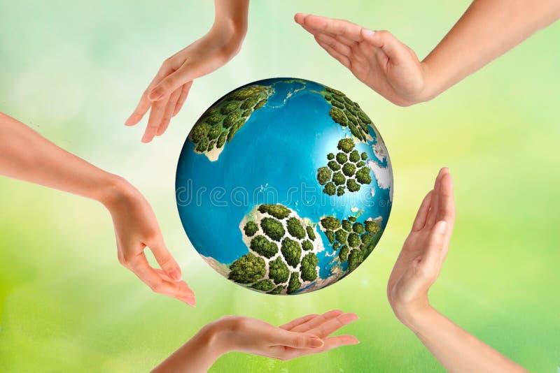 人们、和平、爱、生活和环境概念-关闭显示在地球地球的人的手心形姿态和 免版税库存照片