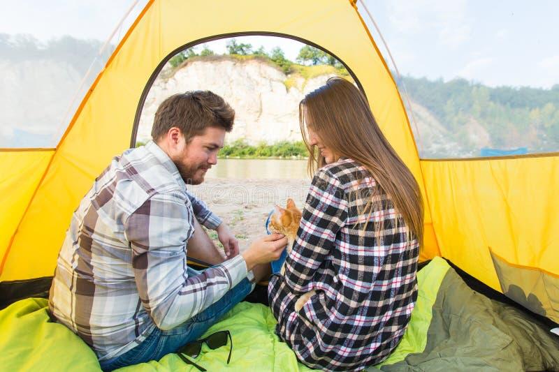 人们、夏天旅游业和自然概念-年轻夫妇从里边休息在野营的帐篷的,看法 免版税图库摄影