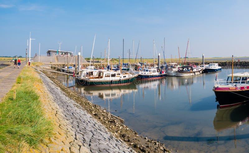 人们、汽艇和风船在西部弗里斯兰省人海岛斯希蒙尼克岛,荷兰小游艇船坞  免版税库存照片