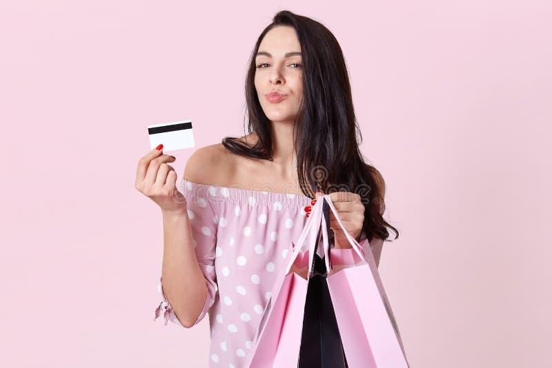 人们、购物、销售和财务概念 有被折叠的嘴唇的俏丽的妇女,拿着购物带来并且显示信用卡,更喜欢 免版税库存图片