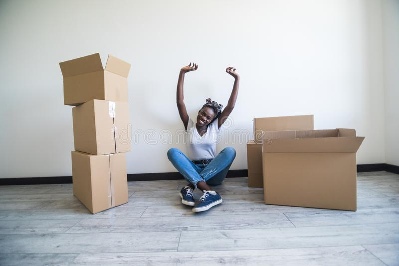 人们、运动的新的地方和修理概念-坐在新的公寓和举在喜悦的愉快的非裔美国人的年轻女人胳膊 免版税库存照片