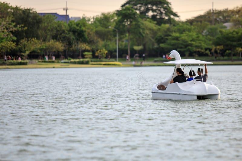 人们乘坐鸭子小船在公园名字Suan Luang Rama IX在日落时间曼谷,泰国 免版税库存照片